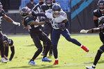 Tennessee Titans running back Derrick Henry (22) stiff arms Jacksonville Jaguars cornerback Sidney Jones, left, during the first half of an NFL football game, Sunday, Dec. 13, 2020, in Jacksonville, Fla. (AP Photo/Phelan M. Ebenhack)