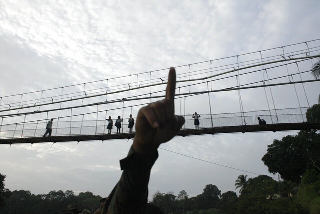 FILE - In this June 19, 2018 file photo, a Panama border police officer points as he begins to patrol in the Darien Province, on the border with Colombia, in Yaviza, Panama. As Panama deals with the care of migrants living in shelters in the jungle province of Darien in May 2020, the Inter-American court ordered Panama to take urgent measures to protect migrants' lives in the midst of the coronavirus pandemic. (AP Photo/Arnulfo Franco, File)