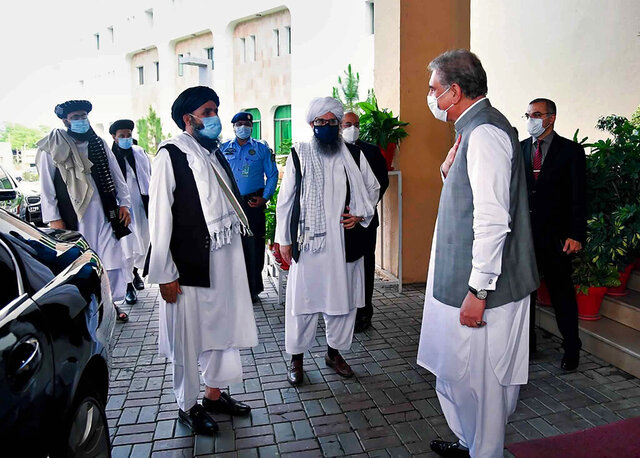 In this photo provided by Pakistan's Ministry of Foreign Affairs, Foreign Minister Shah Mahmood Qureshi, right, greets members of a Taliban political team on their arrival at the Foreign Ministry for talks, in Islamabad, Pakistan, Tuesday, Aug. 25, 2020. The team arrived in Pakistan on Monday as efforts appear to be ramping up to get negotiations underway between the Afghan government and the insurgents. The start of the talks, envisaged under a U.S.-Taliban peace agreement signed in February, was hampered by a series of delays that have frustrated Washington. (Pakistan Ministry of Foreign Affairs via AP)
