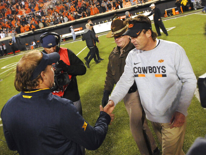 Oklahoma State head coach Mike Gundy, left, shakes the hand of West Virginia head coach Dana Holgorsen following an NCAA college football game in Stillwater, Okla., Saturday, Nov. 17, 2018. Oklahoma State defeated West Virginia 45-41. (AP Photo/Brody Schmidt)