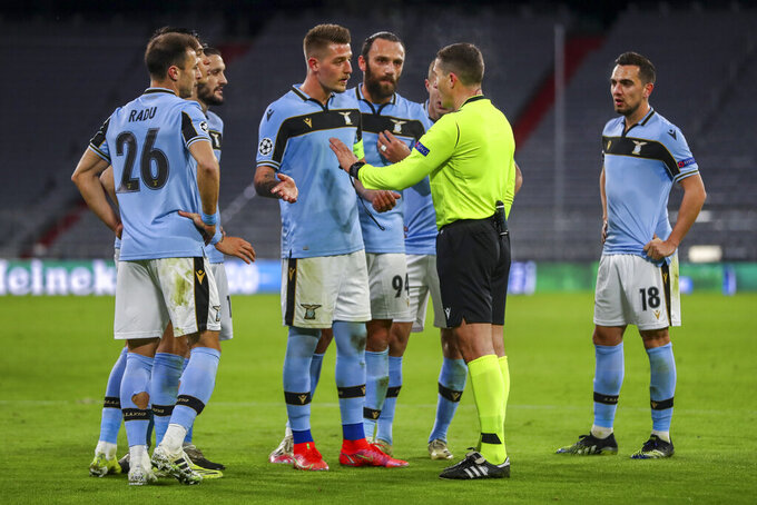 Lazio players argue with the referee during the Champions League, round of 16, second leg soccer match between FC Bayern Munich and Lazio at the soccer Arena stadium in Munich, Germany, Wednesday, March 17, 2021. (AP Photo/Matthias Schrader)