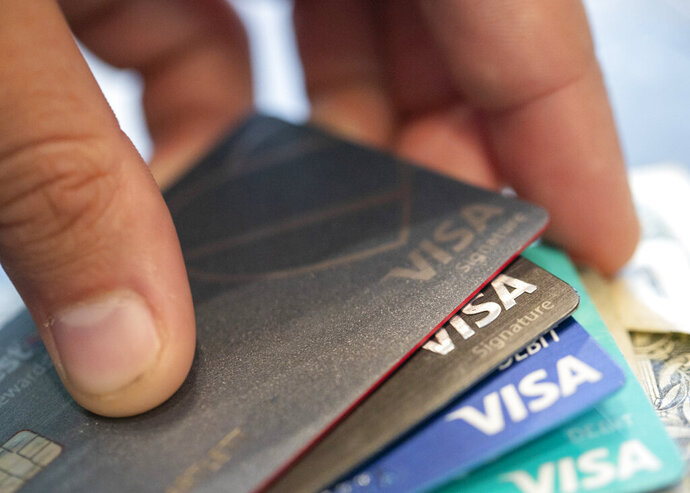 FILE - This Aug. 11, 2019 file photo shows Visa credit cards in New Orleans. U.S. consumers reduced their borrowing for a third straight month in May 2020 as the millions of jobs lost because of the coronavirus pandemic made households less eager to take on new debt. The Federal Reserve reported Wednesday, July 8, 2020 that consumer borrowing declined by $18.3 billion in May, a drop of 5.3%.  (AP Photo/Jenny Kane, File)