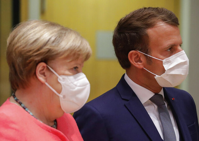 German Chancellor Angela Merkel, left, and French President Emmanuel Macron arrive for a round table meeting at an EU summit in Brussels, Friday, July 17, 2020. Leaders from 27 European Union nations meet face-to-face on Friday for the first time since February, despite the dangers of the coronavirus pandemic, to assess an overall budget and recovery package spread over seven years estimated at some 1.75 trillion to 1.85 trillion euros. (Stephanie Lecocq, Pool Photo via AP)