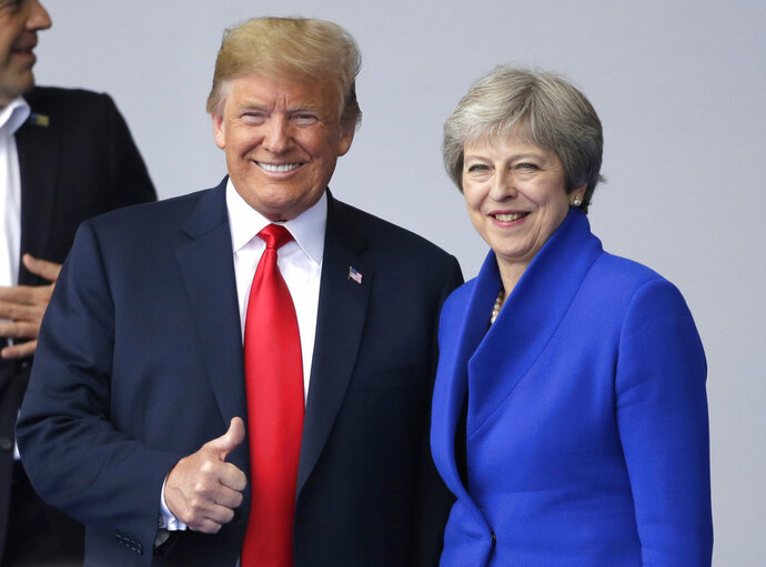 In this July 11, 2018, photo, U.S. President Donald Trump, left, talks to British Prime Minister Theresa May during a summit of heads of state and government at NATO headquarters in Brussels. Trump is all in for Winston Churchill during his first visit to the United Kingdom as president, paying his respects to an icon of American conservatives who coined the phrase the