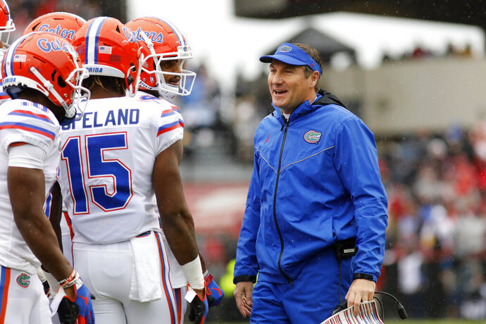 Florida's head coach Dan Mullen smiles with his players during in the first half of an NCAA college football game against South Carolina, Saturday, Oct. 19, 2019, in Columbia, SC. (AP Photo/Mic Smith)