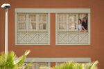Two people look out of a window of the H10 Costa Adeje Palace hotel in La Caleta, in the Canary Island of Tenerife, Spain, Wednesday, Feb. 26, 2020.  Spanish officials say the tourist hotel in Tenerife has been placed in quarantine after an Italian doctor staying there tested positive for the COVID-19 virus and Spanish news media says some 1,000 tourists staying at the complex are not allowed to leave. (AP Photo)
