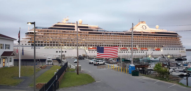 In this Monday, June 15, 2020 photo, the cruise ship Oceania Riviera is tied up in Eastport, Maine. Cruise lines stopped sailing in mid-March after several high-profile outbreaks of COVID-19 in ships at sea, and thousands of cruise ship workers are still stuck at sea. The Riviera arrived Sunday in Eastport for an indefinite stay. (Chris Gardner/Port of Eastport, via AP)