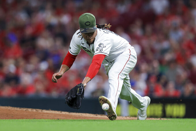 Cincinnati Reds' Luis Castillo fields a ball hit by Los Angeles Dodgers' Trea Turner, who was out at first during the fourth inning of a baseball game in Cincinnati, Friday, Sept. 17, 2021. (AP Photo/Aaron Doster)