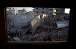 Palestinians inspect the damaged building of Said al-Mis'hal cultural center after it was hit bombed by an Israeli airstrike in Gaza City, Thursday, Aug. 9, 2018. Palestinian officials say Israeli warplanes have attacked the cultural center in Gaza City. The Palestinian Health Ministry says seven bystanders were wounded in Thursday evening's airstrike in the Shati refugee camp. (AP Photo/Khalil Hamra)