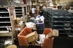 In this Wednesday, May 6, 2020, photo, United States Postal Service carrier Henrietta Dixon sorts mail to be delivered before she sets out on her route in Philadelphia. Dixon has been with the post office for nearly 30 years, the last nine on her current route. (AP Photo/Matt Rourke)