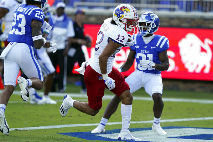 Kansas wide receiver Torry Locklin (12) scores a touchdown as Duke cornerback Josh Blackwell (31) looks on during the first half of an NCAA college football game in Durham, N.C., Saturday, Sept. 25, 2021. (AP Photo/Gerry Broome)