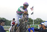 In a photo provided by Equi-Photo, jockey Florent Geroux sponges cool water onto the head of Mandaloun after their win in the $1 million Haskell Stakes horse race through disqualification of Hot Rod Charlie, with jockey Flavien Prat, at Monmouth Park in Oceanport, N.J., Saturday, July 17, 2021. (Bill Denver/Equi-Photo via AP)