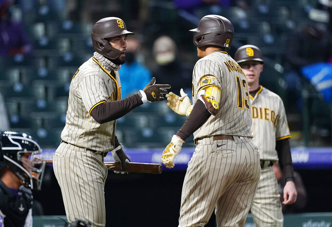 San Diego Padres' Eric Hosmer, left, congratulates Manny Machado on his two-run home run against the Colorado Rockies during the fifth inning of a baseball game Tuesday, May 11, 2021, in Denver. (AP Photo/David Zalubowski)