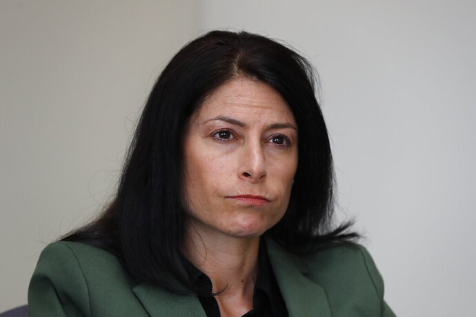 In this June 4, 2019, photo, Dana Nessel, Attorney General of Michigan, listens to a question from reporters in Detroit. Hundreds of boxes. Millions of records. From Texas to Michigan this month, attorneys general are sifting through