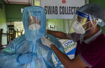 An Indian health worker helps another to wear personnel protection equipment before he collects nasal swab samples at a COVID-19 testing center in Gauhati, Assam state, India, Sunday, July 12, 2020. India is the world's third worst-affected country by the coronavirus. (AP Photo/Anupam Nath)