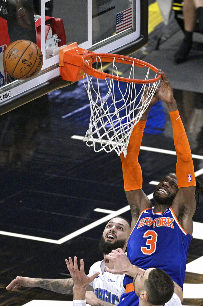 New York Knicks center Nerlens Noel (3) is fouled by Orlando Magic guard Evan Fournier, left, while going for a dunk as Magic center Nikola Vucevic, front, watches during the second half of an NBA basketball game Wednesday, Feb. 17, 2021, in Orlando, Fla. (AP Photo/Phelan M. Ebenhack)