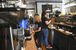 Teen workers Mikayla Crouthamel, 17, (front) and Courtney Collins, 19, (back) along with Elizabeth Bonifati, work at Harvest Moon Coffee & Chocolates in Tarentum on Friday, July 16, 2021. (Kristina Serafini/Pittsburgh Tribune-Review via AP)