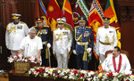 Sri Lankan President Gotabaya Rajapaksa speaks, watched by his brother and Prime Minister Mahinda Rajapaksa in Colombo, Sri Lanka, Friday, Nov. 22, 2019. Rajapaksa, who was elected last week, said he would call a parliamentary election as early as allowed. The parliamentary term ends next August, and the constitution allows the president to dissolve Parliament in March and go for an election. (AP Photo/Eranga Jayawardena)