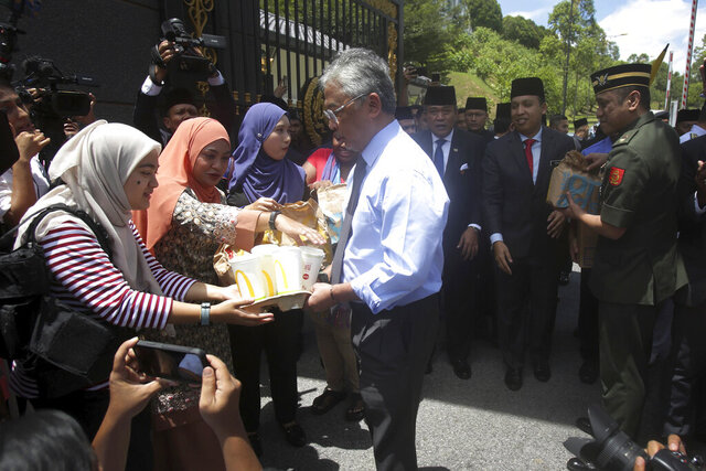 Malaysia's King Sultan Abdullah Sultan Ahmad Shah, center, hands out food parcels to reporters who was camped outside the palace following the resignation of Prime Minister Mahathir Mohamad, in Kuala Lumpur, Tuesday, Feb. 25, 2020. After months of resisting pressure to hand over the premiership to his named successor, Mahathir Mohamad finally quit this week. But in a confounding twist, the 94-year-old leader emerged stronger than before, while his ruling alliance, which won a historic vote about two years ago, met its Waterloo. (AP Photo)
