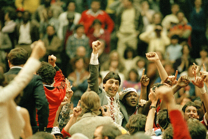 """FILE - In this April 4, 1983, file photo, North Carolina State coach Jim Valvano, center with fist raised, celebrates after his basketball team defeated Houston to win the NCAA Final Four championship in Albuquerque, N.M. A student from N.C. State University has kept alive a tradition associated with postseason college basketball. Max Goren produced his own version of """"One Shining Moment,"""" similar to the video that CBS Sports showcases at the end of the men's national championship game -- which would have been played Monday if not for the COVID-19 pandemic.  (AP Photo/File)"""
