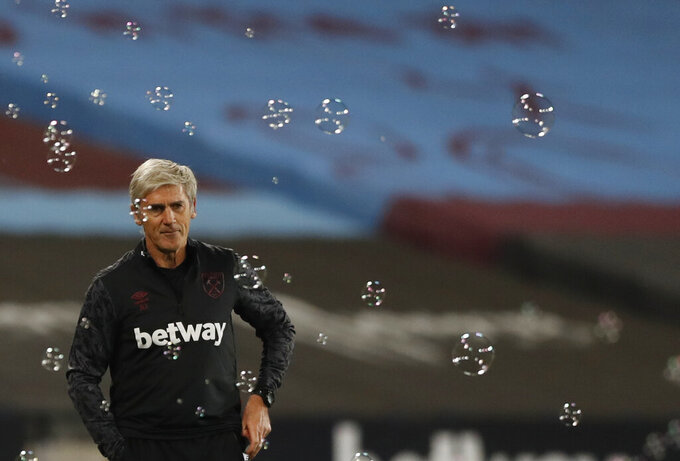 West ham United assistant manager Alan Irvine, left, looks out during the English League Cup soccer match between West Ham and Hull City at the London Stadium in London, Tuesday, Sept. 22, 2020. (AP Photo/Alastair Grant, Pool)