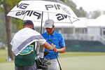 Defending champion Cameron Champ, right, and his caddie, protect his clubs on the ninth green as a weather warning is sounded during the opening round of the Sanderson Farms Championship golf tournament in Jackson, Miss., Thursday, Sept. 19, 2019. Play was stopped. (AP Photo/Rogelio V. Solis)
