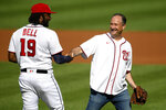 Doug Emhoff, second gentleman of the United States, right, shakes hands with Washington Nationals first baseman Josh Bell (19) after he threw out the ceremonial first pitch before a baseball game between the Nationals and the Colorado Rockies, Saturday, Sept. 18, 2021, in Washington. (AP Photo/Nick Wass)