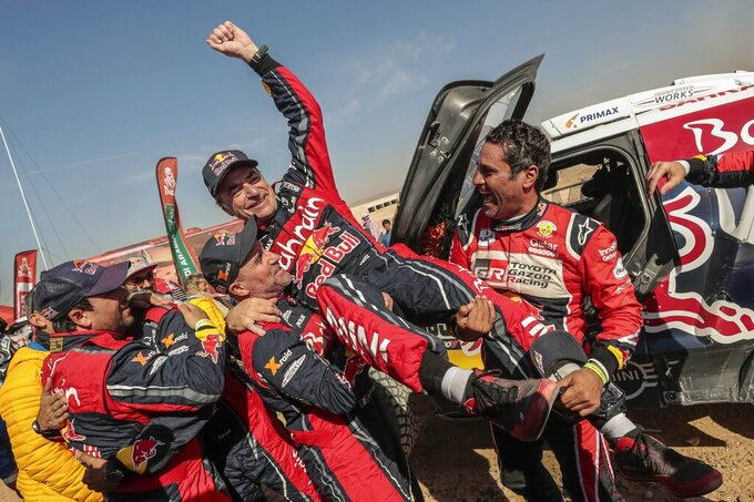 Driver Carlos Sainz, of Spain, center, is lifted by Driver St»phane Peterhansel, of France, center and left, and driver Nasser Al-Attiyah, of Qatar, center and right, at the end of stage twelve of the Dakar Rally between Haradth and Qiddiya, Saudi Arabia, Friday, Jan. 17, 2020. (AP Photo/Bernat Armangue)