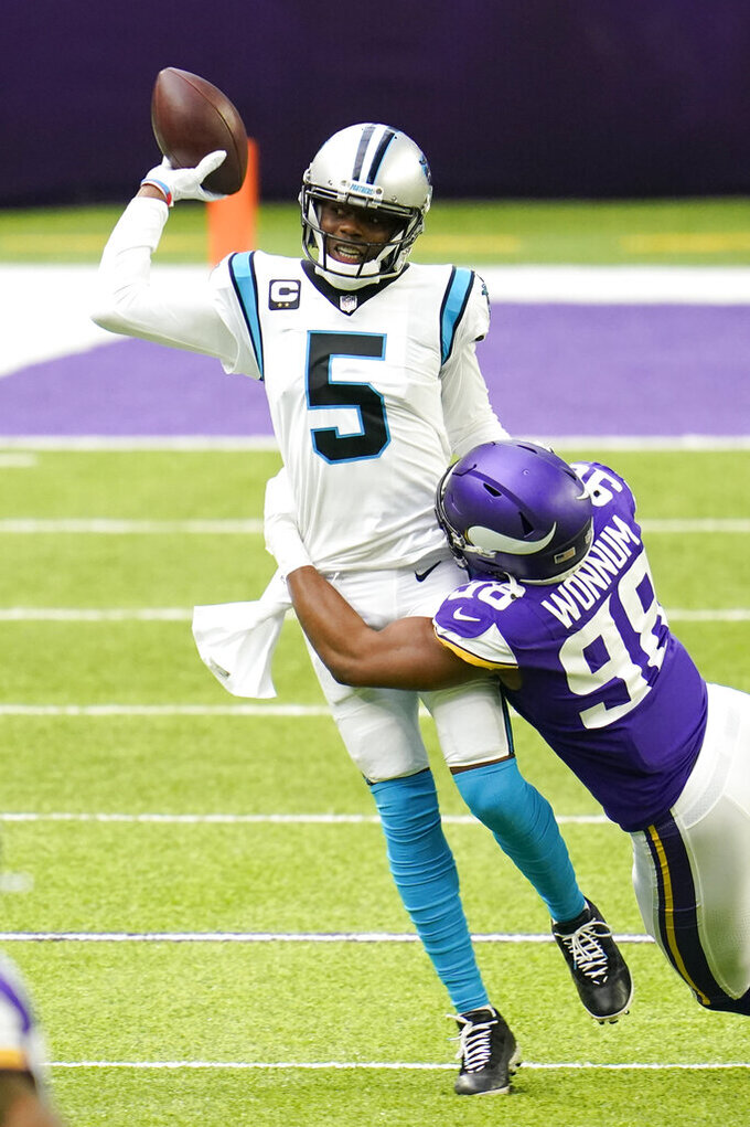 Carolina Panthers quarterback Teddy Bridgewater (5) tries to break a tackle by Minnesota Vikings defensive end D.J. Wonnum during the first half of an NFL football game, Sunday, Nov. 29, 2020, in Minneapolis. (AP Photo/Jim Mone)