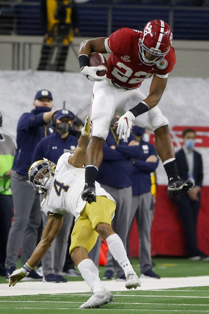 Alabama running back Najee Harris (22) hurdles Notre Dame cornerback Nick McCloud (4) as he carries the ball for a long gain in the first half of the Rose Bowl NCAA college football game in Arlington, Texas, Friday, Jan. 1, 2021. (AP Photo/Michael Ainsworth)