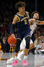 Michigan's Jordan Poole, left, breaks free of Minnesota's Gabe Kalscheur as he drives in the second half of an NCAA college basketball game Thursday, Feb. 21, 2019, in Minneapolis. (AP Photo/Jim Mone)