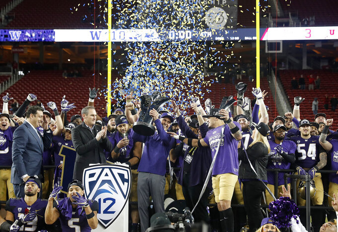 Washington coach Chris Petersen, center, raises the trophy as he celebrates with his players after a 10-3 win over Utah in the Pac-12 Conference championship NCAA college football game in Santa Clara, Calif., Friday, Nov. 30, 2018. (AP Photo/Tony Avelar)
