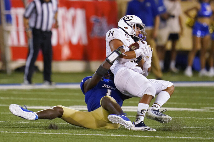 UC Davis running back Ulonzo Gilliam Jr. (34) is brought down by Tulsa safety Kendarin Ray (1) during the second half of an NCAA college football game Thursday, Sept. 2, 2021, in Tulsa, Okla. (AP Photo/Sue Ogrocki)
