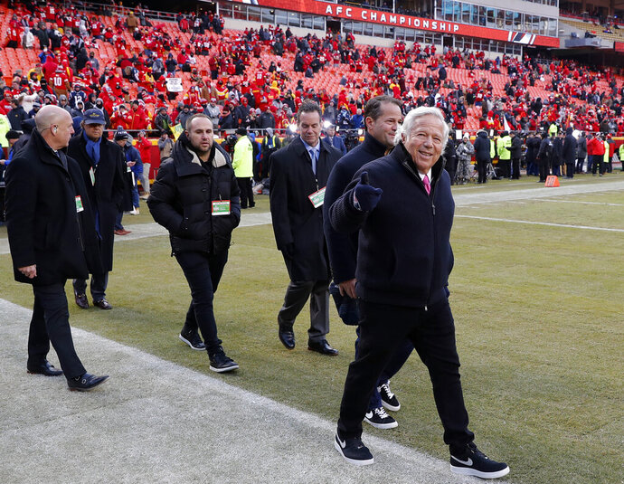 FILE - In this Jan. 20, 2019, file photo, New England Patriots owner Robert Kraft, right, arrives on the field before the AFC Championship NFL football game between the Kansas City Chiefs and the New England Patriots, in Kansas City, Mo. Patriots owner Robert Kraft visited a Florida massage parlor for sex acts on the morning of the AFC Championship Game, which he attended in Kansas City later that day. It was his second visit to the parlor in less than 24 hours, according to documents released by the Palm Beach State Attorney's Office Monday afternoon, Feb. 25, 2019. (AP Photo/Charlie Neibergall, File)