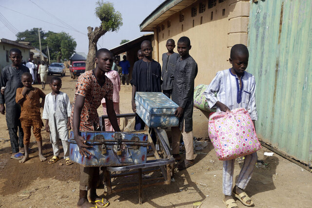Habubakar Liti, left, Bello Ibrahim, centre, and Isah Nasir, recently released students, arrive back home carrying boxes containing their school belongings in Ketare, Nigeria, Saturday Dec. 19, 2020. Nigeria's freed schoolboys have reunited with their joyful parents after being held captive for nearly a week by gunmen allied with jihadist rebels in the country's northwest. Relieved parents hugged their sons tightly on Saturday in Kankara, where more than 340 boys were abducted from the Government Science Secondary school on the night of Dec. 11. (AP Photo/Sunday Alamba)