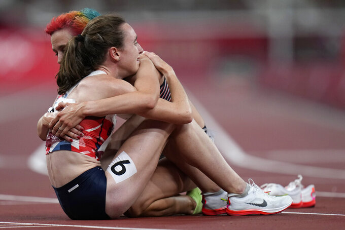 Laura Muir, of Britain, is embraced by a competitor after her second place finish in the final of the women's 1,500-meters at the 2020 Summer Olympics, Friday, Aug. 6, 2021, in Tokyo. (AP Photo/Petr David Josek)