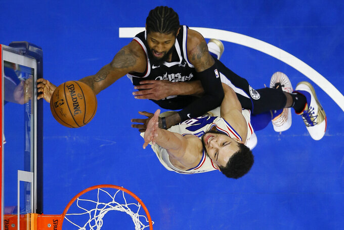 Los Angeles Clippers' Paul George, top, goes up for a shot against Philadelphia 76ers' Ben Simmons during the second half of an NBA basketball game, Friday, April 16, 2021, in Philadelphia. (AP Photo/Matt Slocum)