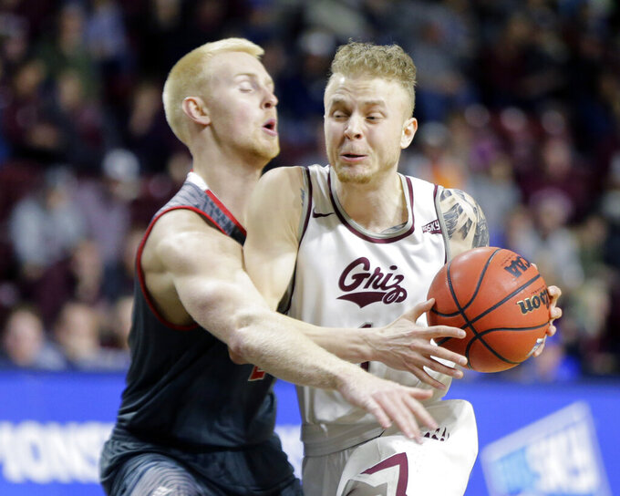 Montana's Timmy Falls moves the ball around Eastern Washington's Ty Gibson during an NCAA college basketball game in the championship of the Big Sky Tournament in Boise, Idaho, Saturday, March 16, 2019. (AP Photo/Otto Kitsinger)