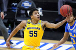 Michigan guard Eli Brooks (55) drives to the basket ahead of UCLA guard UCLA Bruins guard Johnny Juzang (3) during the first half of an Elite 8 game in the NCAA men's college basketball tournament at Lucas Oil Stadium, Tuesday, March 30, 2021, in Indianapolis. (AP Photo/Darron Cummings)