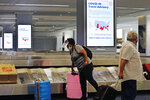 An arriving passenger wearing a face shield, left, collects her luggage in the baggage claim area of LaGuardia Airport's Terminal B, Thursday, June 25, 2020, in New York. New York, Connecticut and New Jersey are asking visitors from states with high coronavirus infection rates to quarantine for 14 days. The