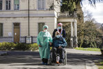 Palmiro Tami, 82, is carried on wheelchair by director Maria Giulia Madaschi, flanked by his wife Franca Persico in the garden of the Fondazione Martino Zanchi nursing home, after receiving the second shot of Moderna COVID-19 Vaccine, in Alzano Lombardo, northern Italy, Monday, March 22, 2021. Italy's nursing homes have been declared an initial success in an otherwise lagging vaccine campaign. At a nursing home near Bergamo, one 82-year-old resident received his second jab, and a surprise visit from his 77-year-old wife. Their last hug had been through plastic on his birthday, in February. (AP Photo/Luca Bruno)