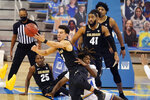 Colorado guard Maddox Daniels (3) grabs a loose ball over UCLA forward Jalen Hill during the first half of an NCAA college basketball game Saturday, Jan. 2, 2021, in Los Angeles. (AP Photo/Marcio Jose Sanchez)