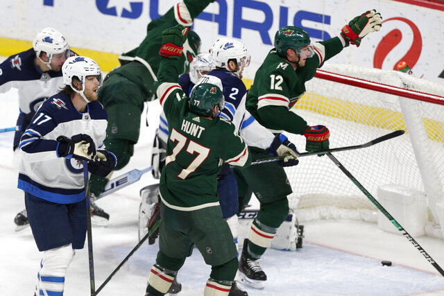 Minnesota Wild center Eric Staal (12) celebrates his goal on Winnipeg Jets goalie Connor Hellebuyck (31) while Winnipeg Jets defenseman Anthony Bittetto (2) and Winnipeg Jets center Adam Lowry (17) look on with Minnesota Wild defenseman Brad Hunt (77) and Minnesota Wild defenseman Zach Parise in on the play in overtime of an NHL hockey game Saturday, Jan. 4, 2020, in St. Paul, Minn. The Wild defeated the Jets 3-2. (AP Photo/Andy Clayton-King)
