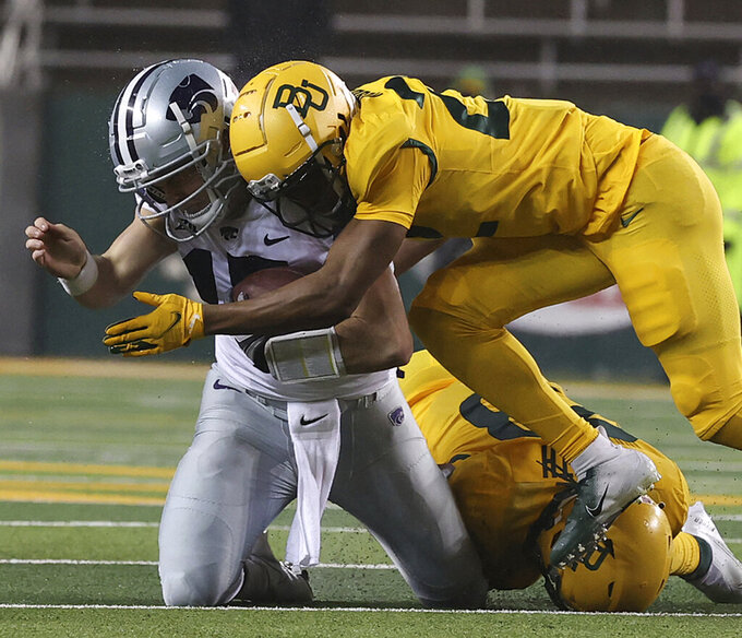 Kansas State quarterback Will Howard (15) is hit in the helmet by Baylor safety JT Woods (22) in the first half of an NCAA college football game, Saturday, Nov. 28, 2020, in Waco, Texas. Woods was ejected from the game for targeting. (Jerry Larson/Waco Tribune-Herald via AP)