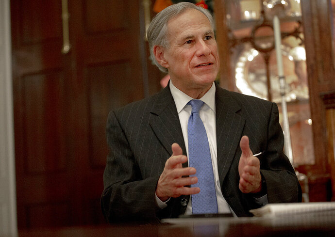 FILE - In this Dec. 6, 2018 file photo, Texas Gov. Greg Abbott speaks during an interview at the Texas Governor's Mansion, in Austin, Texas. Texas lawmakers moved the state closer to putting more armed teachers in schools, sending the measure to Abbott for consideration. The bill passed Wednesday night, May 22, 2019, by the Senate was part of a group of school safety measures filed after a gunman killed eight students and two substitute teachers at Santa Fe High School outside of Houston in May 2018. (Nick Wagner/Austin American-Statesman via AP, File)