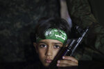 A boy holds a weapon as he stands beside Hamas militants during a rally in Gaza City, Wednesday, June 9, 2021. Hamas militants held a rally to commemorate the members of the group who were killed in an 11-day war with Israel in May. (AP Photo/Felipe Dana)