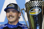 FILE - In this Nov. 16, 2018, file photo, Brett Moffitt stands with his trophy in Victory Lane after winning the NASCAR Truck Series auto racing season championship, at Homestead-Miami Speedway in Homestead, Fla.  Brett Moffitt, Ross Chastain, Austin Hill, Johnny Sauter, Stewart Friesen, Tyler Ankrun, Grant Enfinger and Matt Crafton  are competing in the NASCAR Truck Series playoffs.(AP Photo/Terry Renna, File)