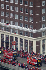 Busses carrying members of the Kansas City Chiefs travel in a parade through downtown Kansas City, Mo., Wednesday, Feb. 5, 2020m to celebrate the Chiefs victory in the NFL's Super Bowl 54. (AP Photo/Charlie Riedel)