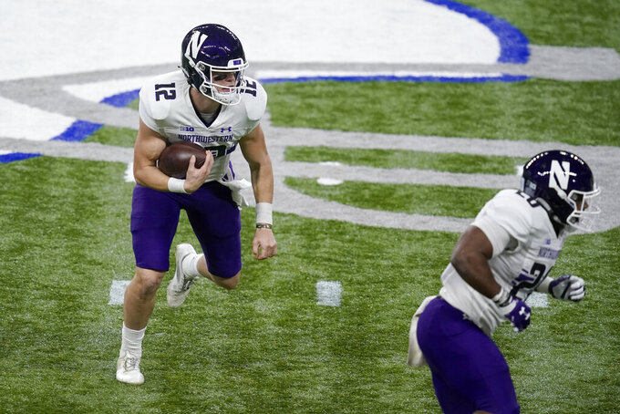 Northwestern quarterback Peyton Ramsey (12) scrambles during the first half of the Big Ten championship NCAA college football game against Ohio State, Saturday, Dec. 19, 2020, in Indianapolis. (AP Photo/Darron Cummings)