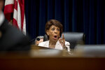 Chairwoman Rep. Maxine Waters, D-Calif. speaks to a colleague as David Marcus, CEO of Facebook's Calibra digital wallet service, testifies before a House Financial Services Committee hearing on Facebook's proposed cryptocurrency on Capitol Hill in Washington, Wednesday, July 17, 2019. (AP Photo/Andrew Harnik)